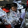 A Syrian refugee boy is wrapped with a thermal blanket after a dinghy carrying Syrian and Afghan refugees deflated some 100m away from the shores of the Greek island of Lesbos, September 13, 2015