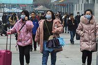 Des passagers arrivant à la Yichang East Railway Station, dans la province de Hubei, portent un masque