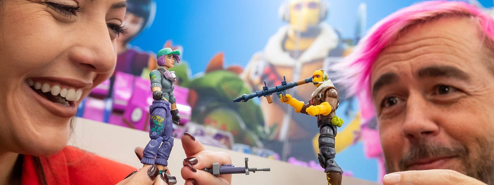 Ashley und Mike präsentieren spielen während der Neuheitenschau der Spielwarenmesse mit zwei Figuren von Jazwares aus dem Action-Building-Spiel Fortnite.
