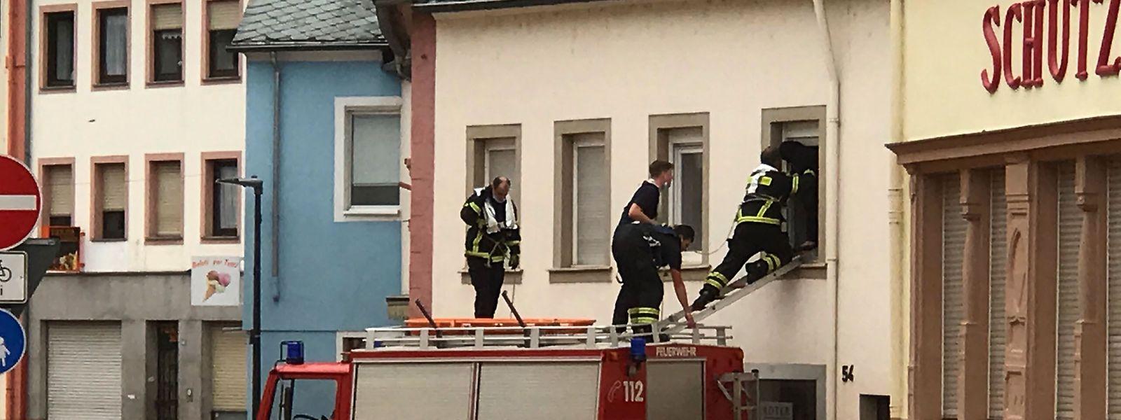 Bombeiros de pé no tejadilho do seu veículo sobem para uma casa inundada no bairro de Ehrang em Trier, no oeste da Alemanha.