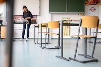 30.04.2020, Baden-Württemberg, Tübingen: Eine Lehrerin bereitet in der Gemeinschaftsschule West Namensschilder für Sitzplätze vor. Ab 4. Mai findet für Abschlussklassen wieder Unterricht statt. Dabei gelten besondere Hygienemaßnahmen, um eine Ansteckung mit dem Coronavirus zu vermeiden. (zu dpa: «Schulen öffnen wieder») Foto: Sebastian Gollnow/dpa +++ dpa-Bildfunk +++