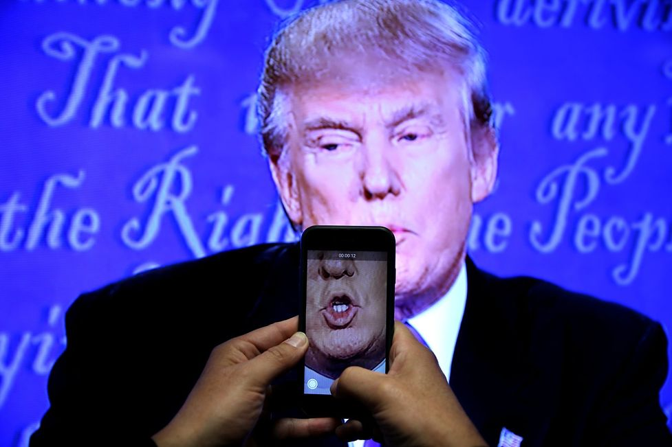 A journalist records a video from screen as Republican U.S. presidential nominee Donald Trump speaks during the first presidential debate