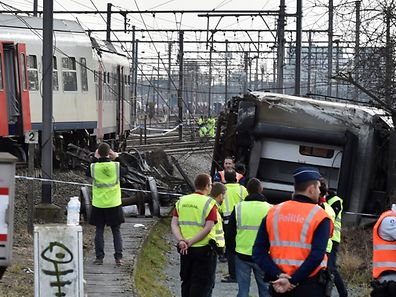Rescuers and police officers stand next to the wreckage of a passenger train after it derailed in Kessel-Lo near Leuven, Belgium February 18, 2017.