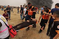 TOPSHOT - Paramedics carry away an injured Palestinian woman protester on a stretcher during clashes with Israeli forces along the border with the Gaza strip east of Gaza City on May 4, 2018, on the sixth straight Friday of mass demonstrations calling for the right to return to their historic homelands. / AFP PHOTO / MAHMUD HAMS