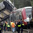 Rescue teams stand next to the site of a train crash in the village of Zoufftgen near Thonville, northeastern France, Wednesday, Oct. 11, 2006. Two trains collided Wednesday close to the border between France and Luxembourg, killing at least five people and trapping others in the crumpled wreckage, officials said. The crash at Zoufftgen in northeast France, about two kilometers (1.2 miles) south of the border, involved a passenger train and a freight train colliding head-on, said France's SNCF rail operator. (AP Photo/Thomas Kienzle)