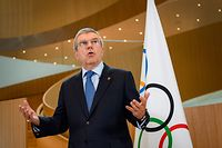 """(FILES) In this file photo taken on March 3, 2020 International Olympic Committee (IOC) President Thomas Bach delivers a statement on the COVID-19 situation during a meeting of the executive board at the IOC headquarters in Lausanne. - Bach said on March 20, 2020 the organisation was """"considering different scenarios"""" for the Tokyo Games, but was optimistic about holding the event as scheduled despite the coronavirus pandemic. (Photo by Fabrice COFFRINI / AFP)"""