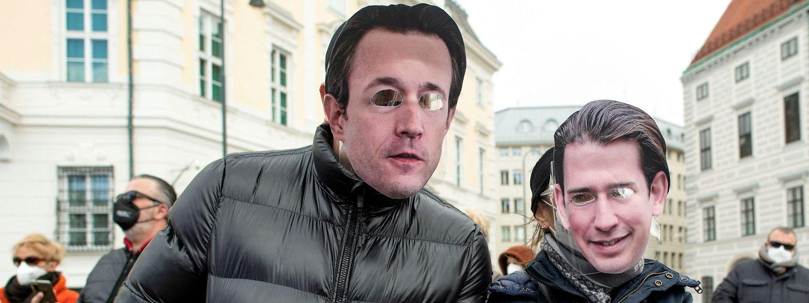 Österreichs Finanzminister Gernot Bluemel (.) und Kanzler Sebastian Kurz - hier Demonstranten mit Masken - sind in die Schusslinie von Kritikern geraten.