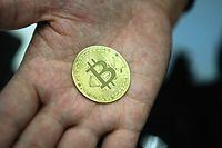 Ein Mann hält eine nachgemachte Münze mit dem Bitcoin-Logo in den Händen.