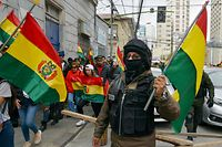 A police officer, who has joined a rebellion, holds a Bolivian national flag during a march to protest against the government in La Paz, Bolivia, on November 9, 2019. - Police in three Bolivian cities joined anti-government protests Friday, in one case marching with demonstrators in La Paz, in the first sign security forces are withdrawing support from President Evo Morales after a disputed election that has triggered riots. (Photo by AIZAR RALDES / AFP)