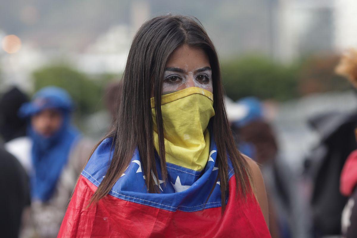Eine Frau hat sich mit einer venezolanischen Flagge maskiert und protestiert gegen den venezolanischen Präsidenten Maduro.