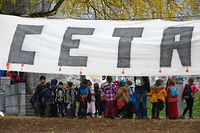 Children walk past a baner hung close to the Walloon parliament in Namur on October 28, 2016.  Parliament in Belgium's Wallonia region approved on October 28, a landmark EU-Canada free trade agreement after marathon talks produced a compromise clearing the way for the European Union to sign the pact. By 58 votes to five, parliament in Namur south of Brussels became the first of the country's three French-speaking communities to back the accord, allowing the Belgian government to give the EU its blessing to go ahead with the deal.  / AFP PHOTO / JOHN THYS