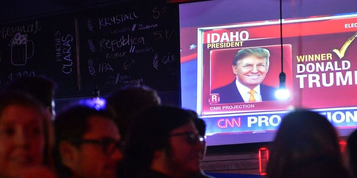 People, including US citizens, gather at a bar as US presidential election results arrive on November 8, 2016 in Mexico City.  Millions of Americans voted November 8th for their new leader in a historic election that will either elevate Democrat Hillary Clinton as their first woman president or hand power to maverick populist Donald Trump. / AFP PHOTO / PEDRO PARDO