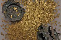 Ein Teil der Münzen mit dem beschädigten Kupfergefäß.