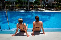 German tourists rest at the swimming pool of the RIU Concordia hotel in Palma de Mallorca on June 15, 2020, as part of a pilot program to reactivate tourism a week before Spain reopens its borders. - Spain, one of the world's leading tourist destinations, will next June 21 re-establish free travel with fellow EU countries. (Photo by JAIME REINA / AFP)