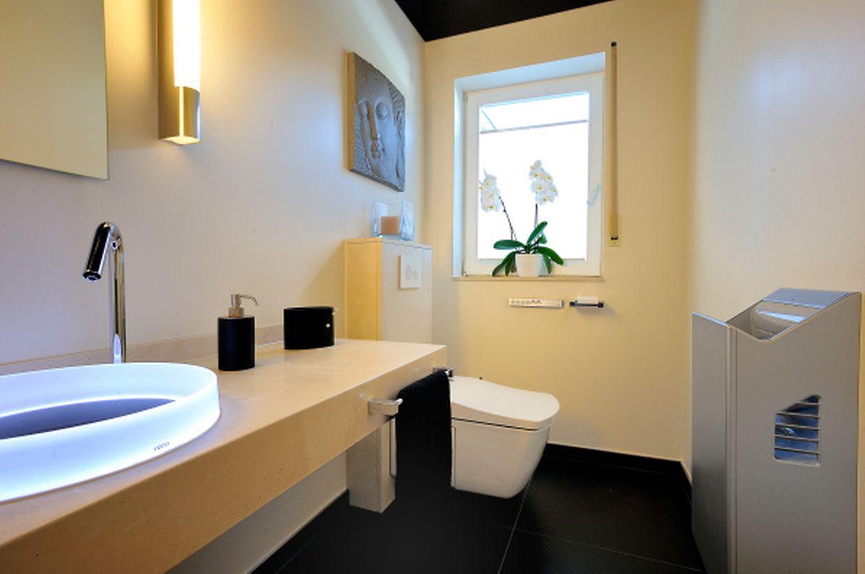 Berührungslos: Dieses moderne Bad mit Dusch-WC verfügt über ein Waschbecken mit Sensortechnik und einen automatischen Händetrockner.