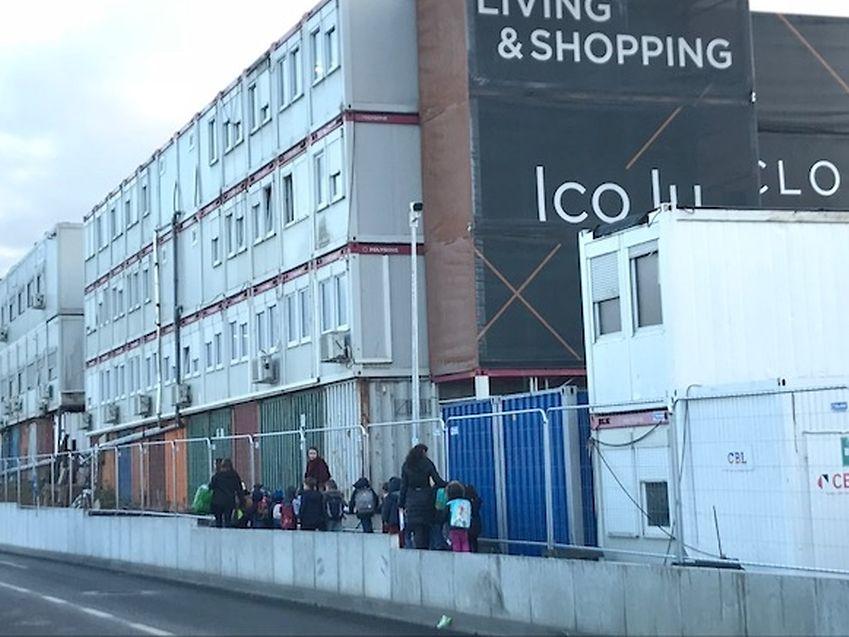 Pour rejoindre le bus de leur foyer scolaire, les enfants doivent marcher sur plusieurs mètres le long de containers de chantier.