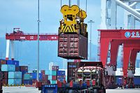 "A container is transferred at a port in Qingdao in China's eastern Shandong province on July 6, 2018. Punishing US tariffs on Chinese imports took effect on July 6, the first shot in what Beijing called ""the largest trade war in economic history"" between the world's top two economies. / AFP PHOTO / - / China OUT"