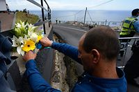 A man on April 18, 2019 puts some flowers at the area where a tourist bus crashed on April 17, 2019 killing 29 in Canico, on the Portuguese island of Madeira. - The Portuguese island of Madeira today began three days of mourning after 29 German tourists died after their bus spun off the road and tumbled down a slope before crashing into a house. (Photo by MIGUEL RIOPA / AFP)