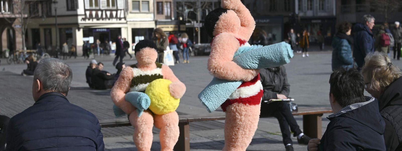 """Straßburg. Im Badeanzug und mit Strandtüchern und Ball ausgestattet machen sich die Straßenkünstler Coco Petitpierre und Yan Cledat, im Rahmen des """"Festival Les Giboulées"""", auf die Suche nach der Sonne. Fotos: AFP"""