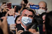 "TOPSHOT - Brazilian President Jair Bolsonaro gestures as he is surrounded by supporters while visiting the residence of an adviser in Bras�lia, on August 23, 2020. - Bolsonaro on Sunday threatened to punch a reporter repeatedly in the mouth after being asked about his wife's links to an alleged corruption scheme. ""I so want to pound your mouth with punches,"" the far-right president said when a reporter from O Globo, posed the question. (Photo by Sergio Lima / AFP)"