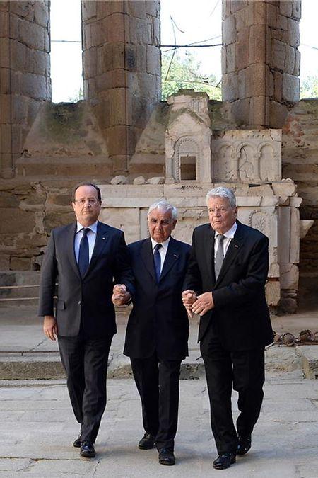 4. September 2013: In der Ruine der abgebrannten Kirche von Oradour stützen Frankreichs Präsident Francois Hollande und der deutsche Bundespräsident Joachim Gauck Robert Hebras, der das Massaker vom 10. Juni 1944 überlebte.