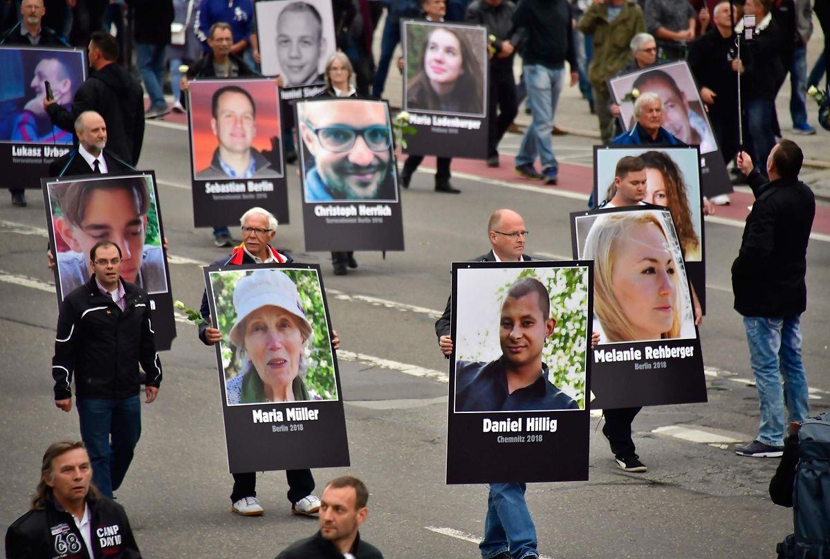 Rechte Demonstranten zeigen Bilder von Menschen, die von Asylbewerbern angegriffen oder getötet wurden.