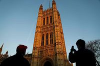 Tourists take photographs of the Victoria Tower, in which the Parliamentary Archives are stored on 12 floors of air-conditioned document storage space, at the south-west end of the Houses of Parliament in Westminster, central London on January 21, 2020. - Prime Minister Boris Johnson suffered another defeat in the unelected House of Lords on Tuesday, over the government's plans for child refugees seeking to join relatives in Britain after Brexit. (Photo by Tolga AKMEN / AFP)
