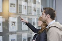 Side view of a young couple looking at window display at real estate office - Image