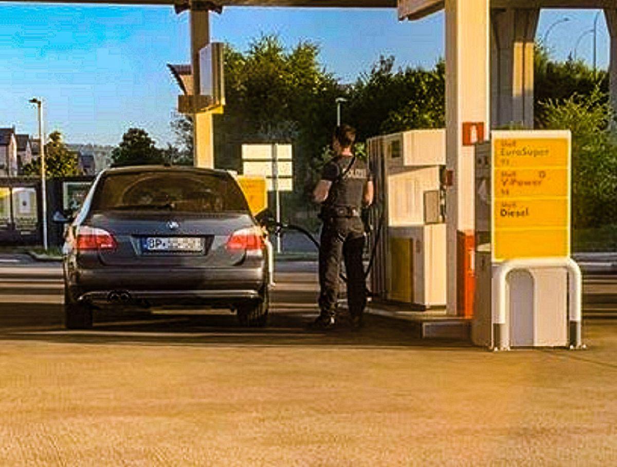 Ein Beamter der deutschen Bundespolizei betankt sein ziviles Dienstfahrzeug trotz Einreisebeschränkungen an einer Tankstelle in Schengen.