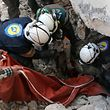 Syrian civil defence volunteers, known as the White Helmets, pull a body from the rubble of a destroyed building on November 19, 2016 following a reported air strike on Aleppo's rebel-held neighbourhood of Bab al-Nayrab.  Intense government air strikes and artillery fire killed at least 27 people in rebel-held parts of Syria's Aleppo, where hospitals have been destroyed and schools forced to close.   / AFP PHOTO / AMEER ALHALBI