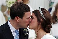 Britain's Princess Eugenie of York (R) and her husband Jack Brooksbank (L) kiss as they emerge from the West Door of St George's Chapel, Windsor Castle, in Windsor, on October 12, 2018 after their wedding ceremony. (Photo by Steve Parsons / POOL / AFP)