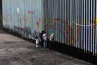 "(FILES) In this file photo taken on January 16, 2019 a family of Central American migrants look through the US-Mexico border fence, as seen from Playas de Tijuana, in Baja California state, Mexico. - President Donald Trump was set February 14, 2019 to declare a ""national emergency"" to help fund hundreds of miles of wall on the southern border to prevent migrants from crossing into the United States illegally from Mexico. The White House said Trump would also sign a spending bill that would avert a government shutdown, but which only provides $1.375 billion for border barriers or fencing -- far from the $5.7 billion Trump wants.Trump has for months teased the idea of declaring a national emergency, which would free up federal money from elsewhere, citing what the administration calls a ""crisis"" at the border. (Photo by Guillermo Arias / AFP)"