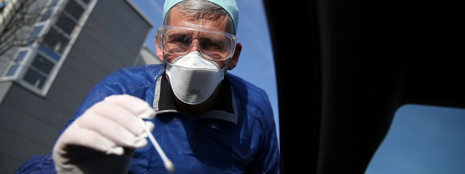 Der Arzt Michael Grosse nimmt bei einer Drive-Through-Teststation in Halle Speichelproben von Autofahrern für Corona-Tests.