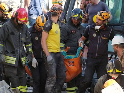 Rescuers carry the body of a victim in the Italian central village of Illica, near Accumoli, on August 24, 2016 after a powerful earthquake rocked central Italy. A powerful pre-dawn earthquake devastated mountain villages in central Italy on August 24, 2016, leaving at least 73 people dead, dozens more injured or trapped under the rubble and thousands temporarily homeless. Scores of buildings were reduced to dusty piles of masonry in communities close to the epicentre of the pre-dawn quake, which had a magnitude of between 6.0 and 6.2, according to monitors.   / AFP PHOTO / MARIO LAPORTA