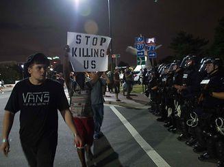 Les manifestants  passent devant la police anti-émeutes lors d'une manifestation contre la violence policière à Charlotte, en Caroline du Nord.