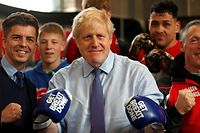 "Britain's Prime Minister and leader of the Conservative Party, Boris Johnson wears boxing gloves emblazoned with ""Get Brexit Done"" as he poses for a photograph at Jimmy Egan's Boxing Academy in Manchester north-west England on November 19, 2019, during a general election campaign trip. - Britain will go to the polls on December 12, 2019 to vote in a pre-Christmas general election. (Photo by Frank Augstein / POOL / AFP)"