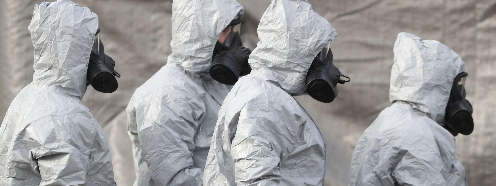 Ermittler in Schutzkleidung und Gasmasken bereiten den Abtransport eines Krankenwagens an einer Station des Sanitätsdienstleisters South Western Ambulance Service in der Nähe von Salisbury vor.