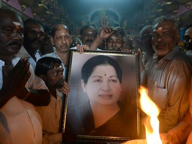 Supporters hold a photograph of Tamil Nadu state leader Jayalalithaa Jayaram as they offer prayers for her at a temple in Mumbai on December 5, 2016.