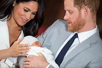 TOPSHOT - Britain's Prince Harry, Duke of Sussex (R), and his wife Meghan, Duchess of Sussex, pose for a photo with their newborn baby son, Archie Harrison Mountbatten-Windsor, in St George's Hall at Windsor Castle in Windsor, west of London on May 8, 2019. (Photo by Dominic Lipinski / POOL / AFP)