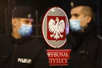 Polish policemen patrol in front of the entrance to the Constitutional Court with the coat of arms of Poland, in Warsaw on October 7, 2021, as the court holds a hearing on the primacy of EU or Polish law. - Poland's top court on October 7 ruled against the supremacy of EU law in a landmark ruling that could threaten the country's EU funding and even its membership of the bloc. (Photo by Jaap Arriens / AFP)