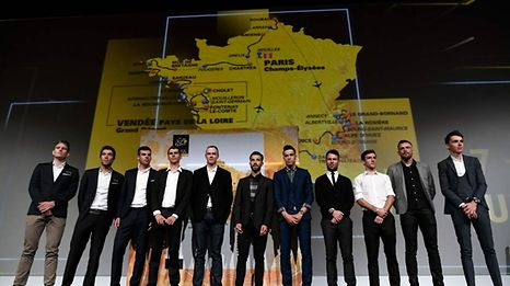 Competitors pose in front of a map of the official route of the 2018 edition of the Tour de France cycling race during its presentation in Paris, on October 17, 2017.