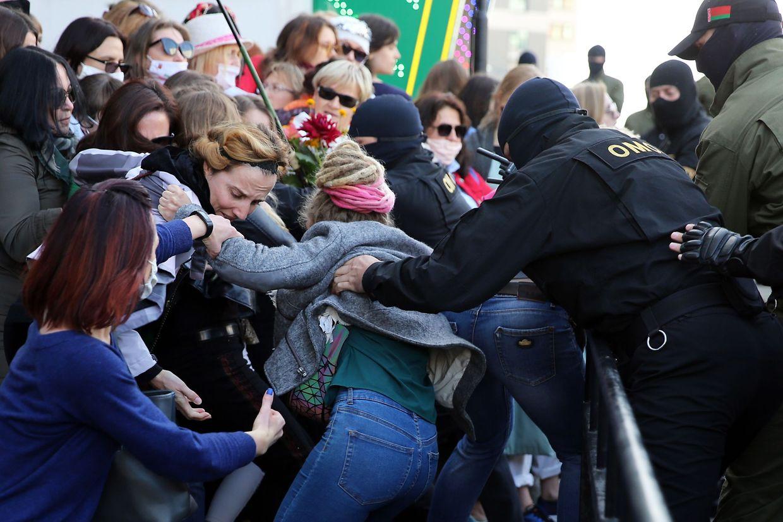 Maskierte Einsatzkräfte greifen Demonstrantinnen aus der Menge.