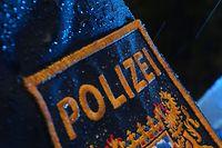 ARCHIV - 15.03.2019, Bayern, Kempten: ILLUSTRATION - Ein Polizist steht im Regen vor einem Streifenwagen, dessen Blaulicht aktiviert ist. Am Freitag beginnt am Landgericht München Ider Prozess gegen zwei Männer, die ältere Menschen als falsche Polizeibeamte um ein Vermögen gebracht haben sollen. Foto: Karl-Josef Hildenbrand/dpa +++ dpa-Bildfunk +++