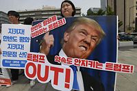 TOPSHOT - A protester holds a placard showing a picture of US President Donald Trump during an anti-Trump rally near the US embassy in Seoul on May 25, 2018. South Korea's Unification Minister said on May 25 that Seoul will press ahead with improving ties with North Korea after US President Donald Trump abruptly cancelled a summit with Pyongyang's leader Kim Jong Un. / AFP PHOTO / Jung Yeon-je