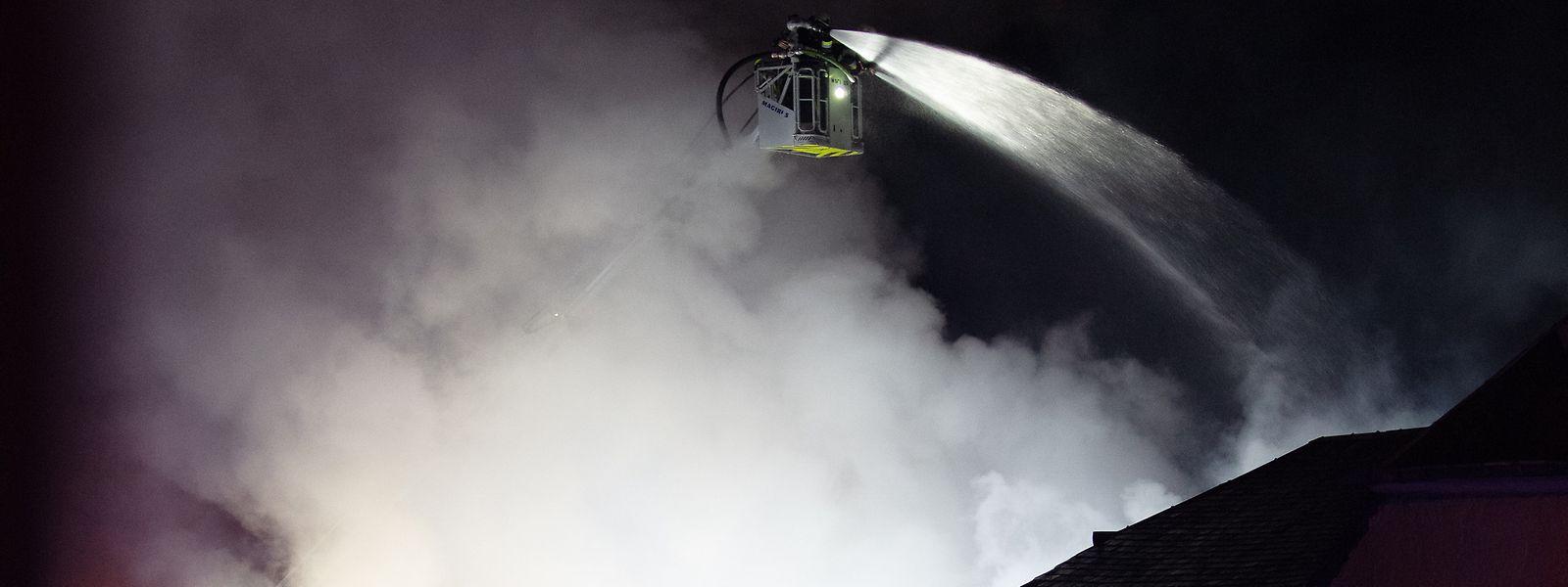 Ein Feuerwehrmann im Löscheinsatz auf einer Drehleiter.
