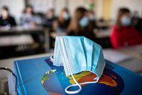 ARCHIV - 17.11.2020, Bayern, München: ILLUSTRATION - Ein Mund- und Nasentschutz liegt im Unterricht in einem Geographie-Seminar in der Jahrgangsstufe elf am staatlichen Gymnasium Trudering auf einem Weltalas, während im Hintergrund die Schülerinnen und Schüler mit Mund- und Nasenschutz zu sehen sind. Bayerns Kultusminister Piazolo (Freie Wähler) hat sich gegen eine Öffnung von Bayerns Schulen nach Ferienende am 10. Januar ausgesprochen. Foto: Matthias Balk/dpa +++ dpa-Bildfunk +++