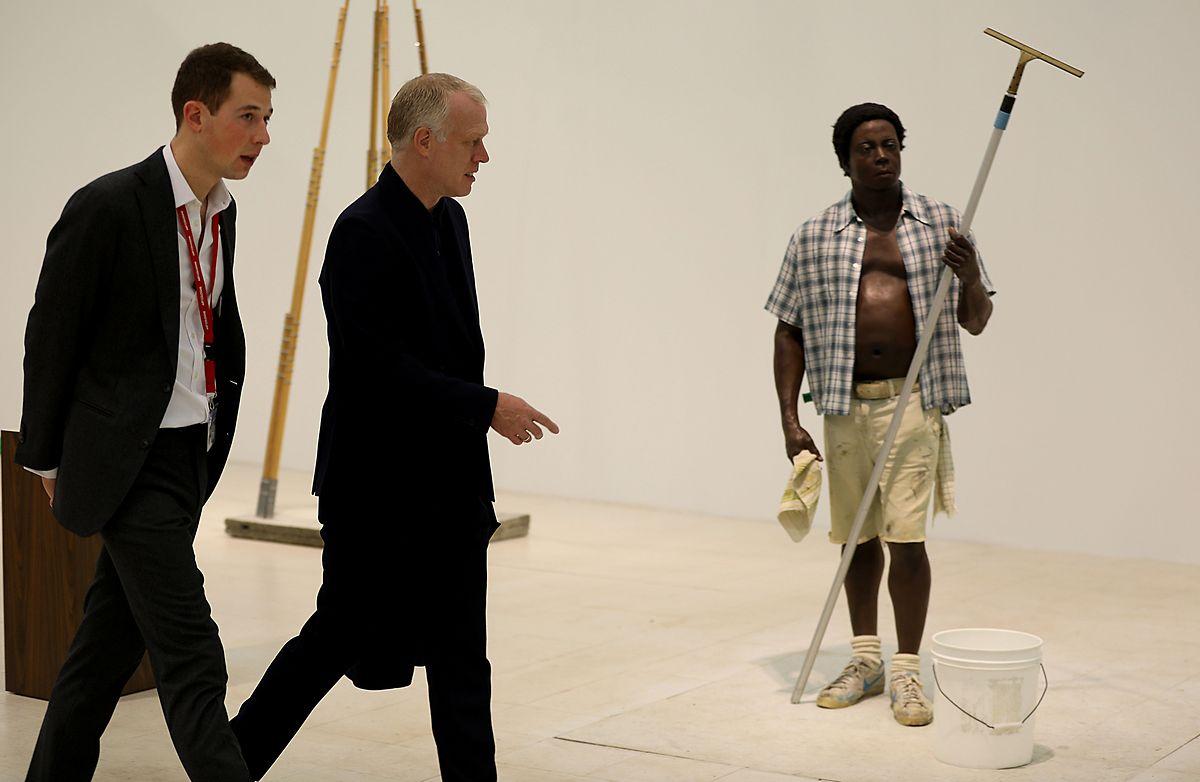 """Daniel Hug (2.v.r.), Direktor der Kunstmesse Art Cologne geht mit dem Galeristen Jona Lueddeckens (l) über den Stand der Galerie Gagosian (USA) am  Kunstwerk """"Window Washer"""" von Duane Hanson vorbei ."""
