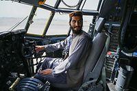 Um soldado talibã senta-se dentro do cockpit de um avião da Força Aérea Afegã no aeroporto de Cabul a 31 de agosto de 2021, depois de os EUA terem retirado todas as suas tropas do país