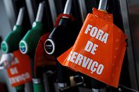 "A placard reading ""Out of service"" hangs at a gas station closed due to the national strike of hazardous goods lorry drivers, on April 17, 2019 in Seixal, in the outskirts of Lisbon. - Many Portuguese were queuing at the few gas stations where it was still possible to refuel despite the shortages caused by a strike of the fuel carriers. (Photo by CARLOS COSTA / AFP)"