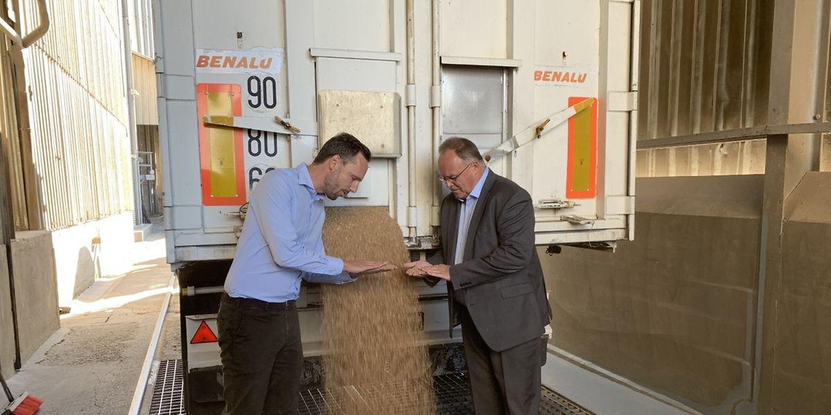 Landwirtschaftsminister Romain Schneider und Jean Muller, Direktor der Moulins de Kleinbettingen, begutachten das angelieferte Getreide.